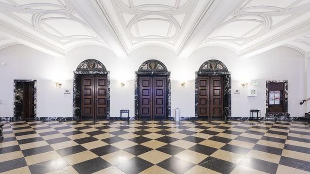 Zu sehen ist die Eingangshalle des Bezirksgerichts Zürich. Der Boden ist schachbrettartig gemustert. Die Halle ist leer. Drei mächtige Holztüren sind geschlossen. Zwei kleinere Türen ebenfalls. Die Decke strahlt weiss.