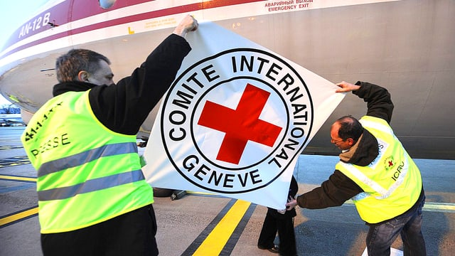 Zwei IKRK-Mitarbeiter kleben eine Folie mit dem Organisations-Emblem auf ein Transportflugzeug.