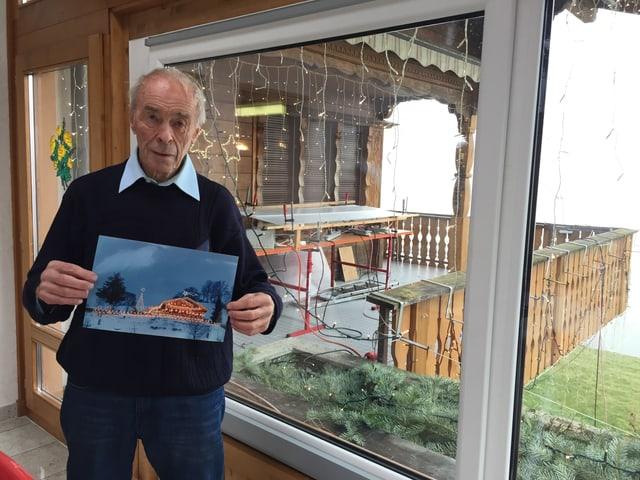 Franz Müller posiert mit einem Bild seines beleuchteten Hauses in der Hand.