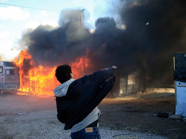 Ein junger Mann steht vor einer brennenden Hütte.