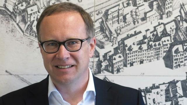 Ein Mann mit Brille vor einem alten Bild der Stadt Luzern.