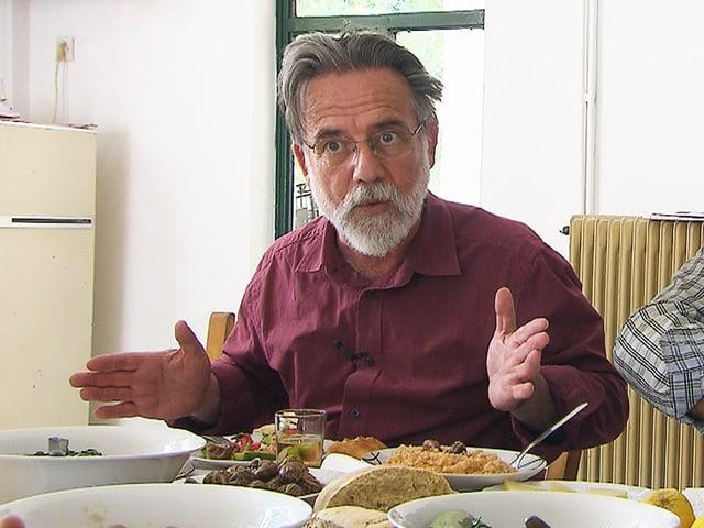 Mann mit Bart an einem Tisch mit Tellern und Esswaren.