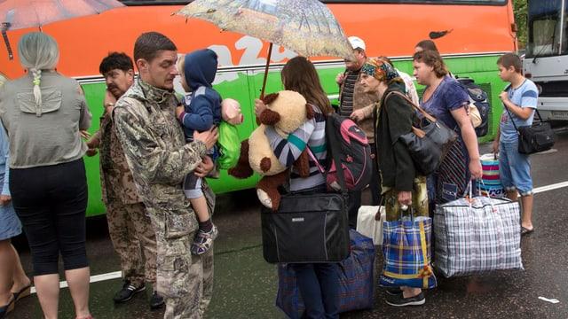 Vertriebene in der Gegend um Slawijansk vor einem Reisebus.