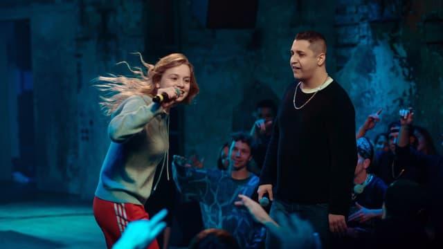 Auf der Bühne in einem Kellerclub: Ein Mädchen singt in ein Mikrofon, ein Mann steht daneben und schaut sie an. Im Hintergrund Menschen, die mit dem Handy filmen.