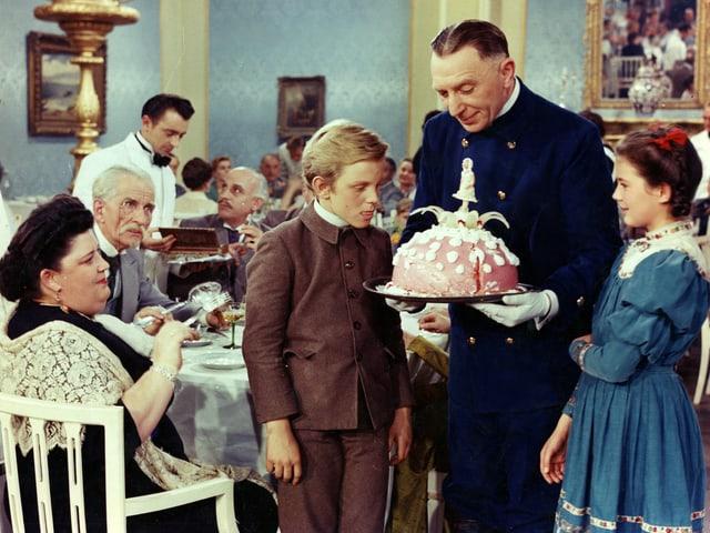 Ein Mann hält einen grossen Kuchen vor sich. Links und rechts davon stehen Peter und Heidi die den Kuchen mit grossen Augen betrachten.