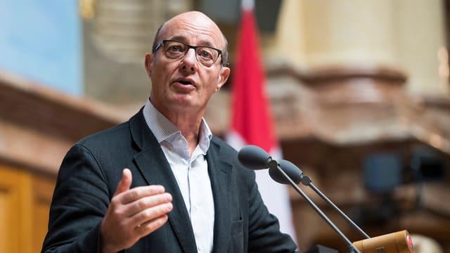 Ein Mann mit Brille am Rednerpult im Parlament.
