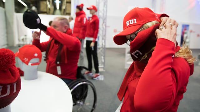 Menschen im Rollstuhl probieren Kleider an.