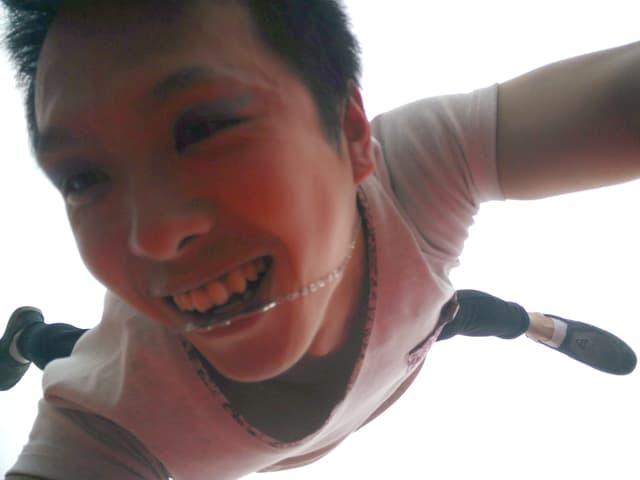 Selfie: Artist im Handstand auf einem Arm von unten aufgenommen.
