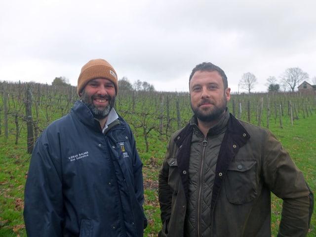 Zwei Männer posieren vor einem Weinberg