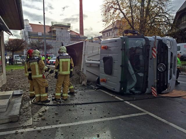 EIn Lastwagen liegt auf der Seite, Feuerwehrmänner stehen daneben.