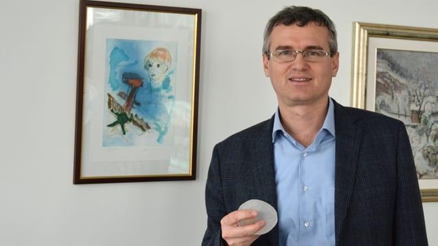 Ein Mann mit Brille hält ein Silikon-Teil in der Hand.
