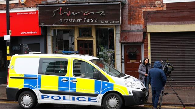 Ein Polizeiauto steht vor einem Gebäude.