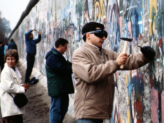 Mehrere Menschen hauen mit Hammern in die Berliner Mauer.
