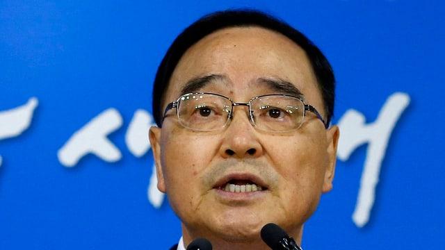 Ein asiatischer Mann mit Brille redet