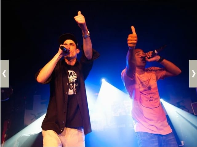 Zu sehen sind zwei Rapper auf der Bühne. Sie halten ein Mikrofon vor ihren Mund und heben den Daumen der anderen Hand.