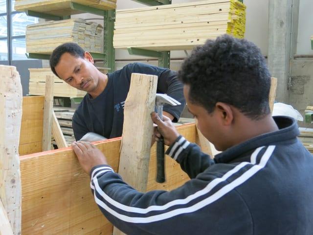 Zwei Männer halten ein Holzbrett.