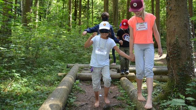 Kinder laufen über Holzstämme.