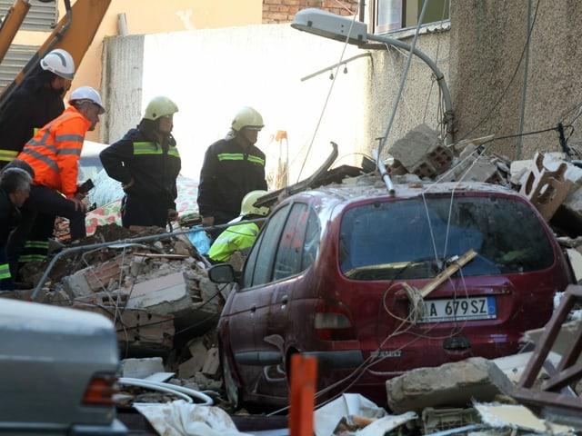 Verschüttetes Auto, Helfer im Hintergrund