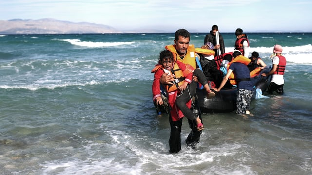 Menschen mit Schwimmwesten besteigen ein Gummiboot. Im Vordergrund Mann mit Schwimmweste, der ein Mädchen trägt.