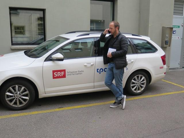 Matthias Haymoz telefoniert vor dem SRF-Auto.