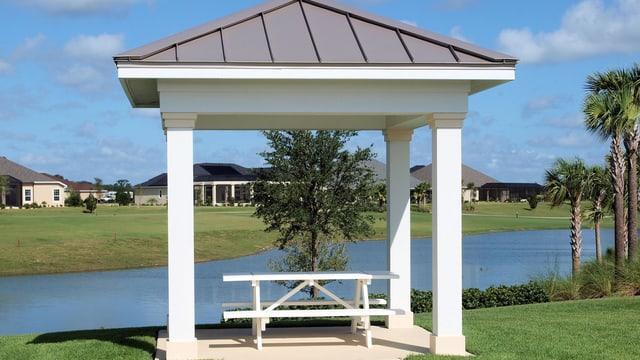 Ein Picknicktisch unter einem Dach einem einem wahrscheinlich künstlich angelegten Fluss mit kurzgeschorenem Rasen.