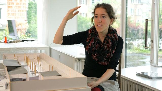 Eine Frau sitzt auf einem Stuhl und gestiluliert mit den Händen.