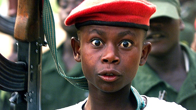 Kämpferische Kindersoldaten im Kongo, schreiend mit Patronengürtel und Gewehren.