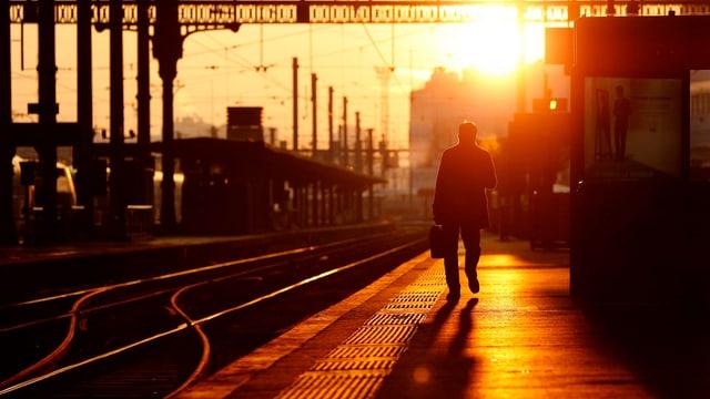 Im Gegenlicht der aufgehenden Sonne ist ein Mann auf einem Perron eines Bahnhofs unterwegs.