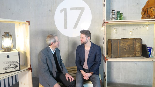 Zwei Herren sitzen auf einer Holzkiste. Über ihren Köpfen die Zahl 17.