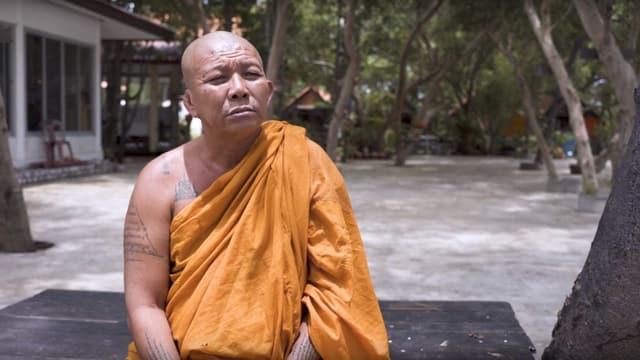 Buddhistischer Mönch sitzt auf einer Bank in seiner Tempelanlage.