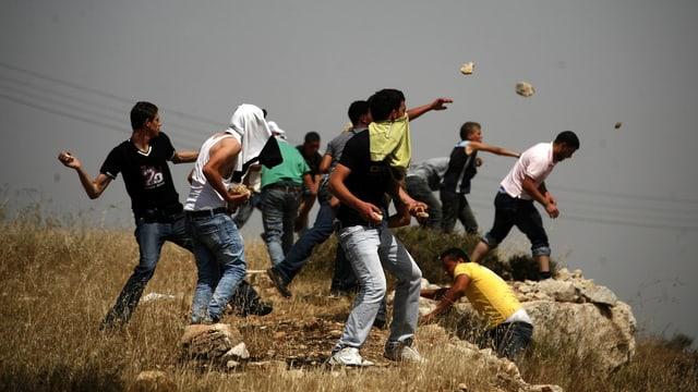 Palästinensische Jugendliche werfen Steine von einem Hügel.