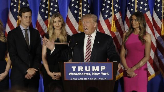 Trump auf einer Bühne, hinter ihm Kushner, Ivanka und Ehefrau Melania.