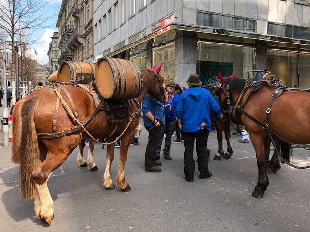 Männer warten mit Pferden in der Stadt.