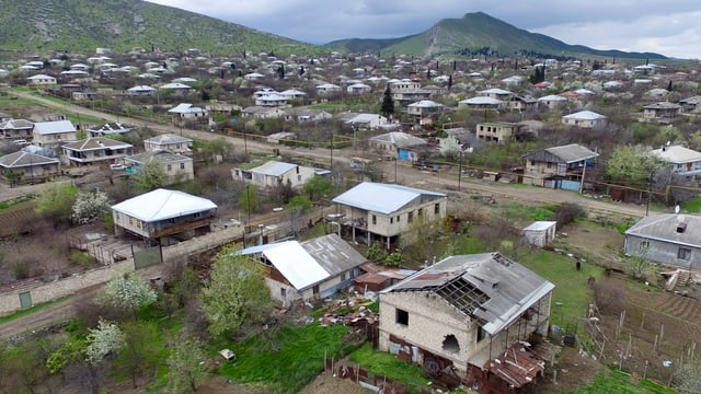 Blick über ein Dorf in der Region Berg-Karabach, im Vordergrund ein beschädigtes Haus