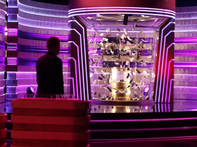 Röbi Koller (Schattenbild) blickt auf den «Happymat» im grell beleuteten Studio.