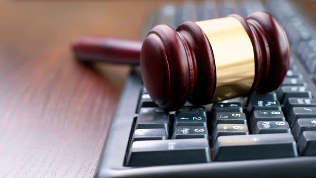 Ein Richterhammer auf einer Tastatur