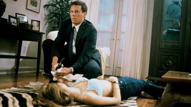 Ein Mann in Anzug kniet neben einer leblosen Frau.
