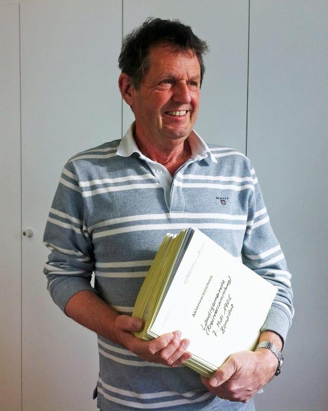 Pierino Casutt hält einen Stapel gelber Karton-Mäppchen in seinen Händen.