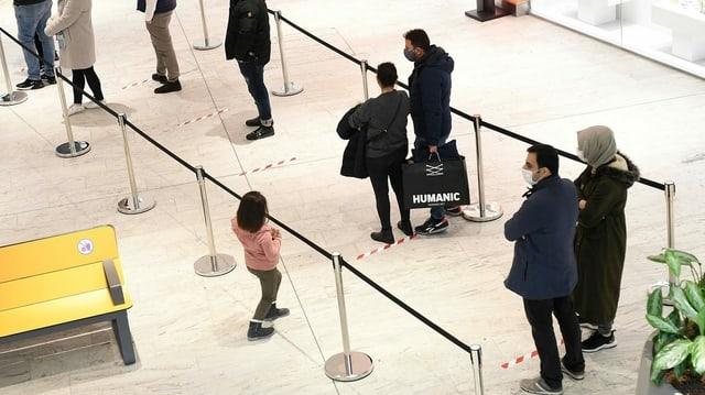 Menschen stehen Schlange in einem Einkaufszentrum.