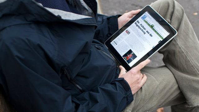 .Mann schaut auf Website 20min.ch auf einem Tablet-Computer
