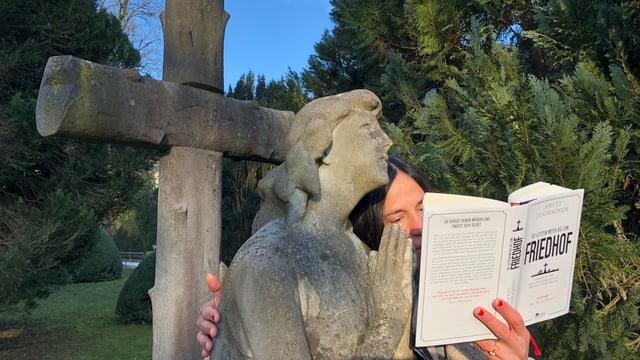 Annette König umarmt eine Friedhofsfigur und hält das Buch «Die letzten Meter bis zum Friedhof» in der Hand.