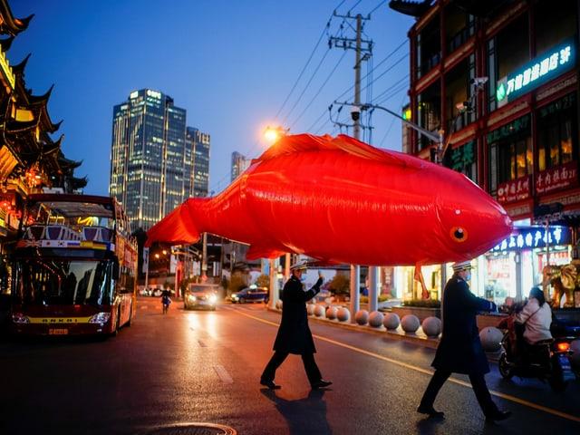 Zwei Männer tragen einen roten aufblasbaren Fisch