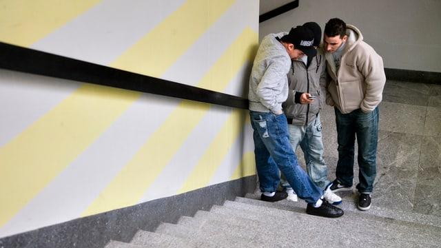 Schüler schauen während einer Pause auf ein Mobiltelefon.