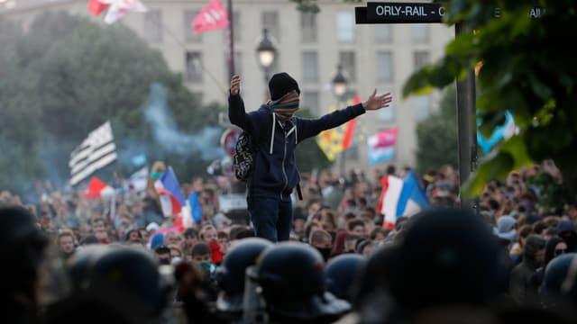 Ein vermummter Demonstrant steht über der Menschenmenge mit ausgebreiteten Armen.