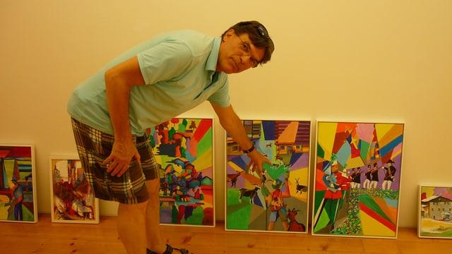 Il pictur-artist Lucas Tomaschett avant che pender si ses maletgs en il Museum Sursilvan Cuort Ligia Grischa