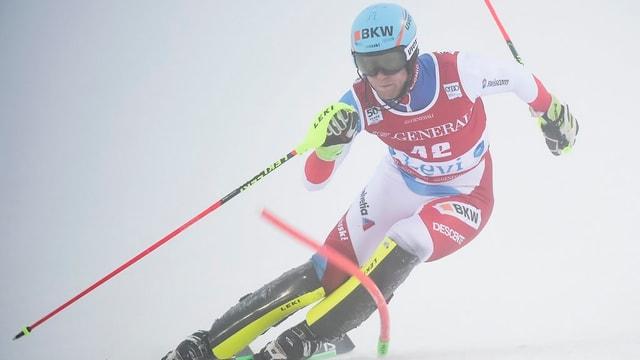 Skifahrer während eines Slaloms. Ansicht von vorne. Slalomstange wird durch Fahrer runtergedrückt.