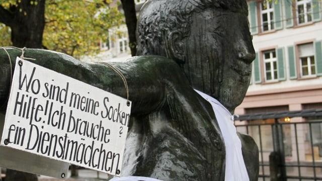 Ein Plakat an einer Statue beim Basler Totentanz