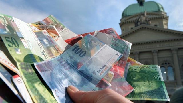 Symbolbild: Eine Hand hält Banknoten, im Hintergrund das Bundeshaus.