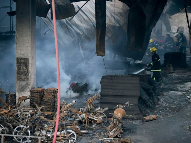 Feuerwehrmann versucht Brandherd zu löschen