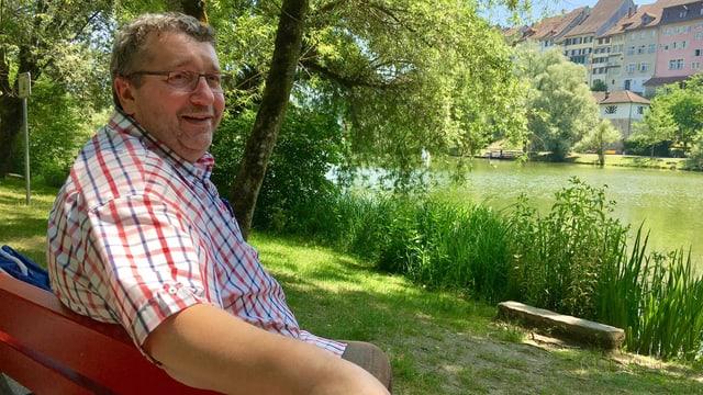 Hans Schmid sitzt auf einer roten Holzbank am Wiler Weiher.